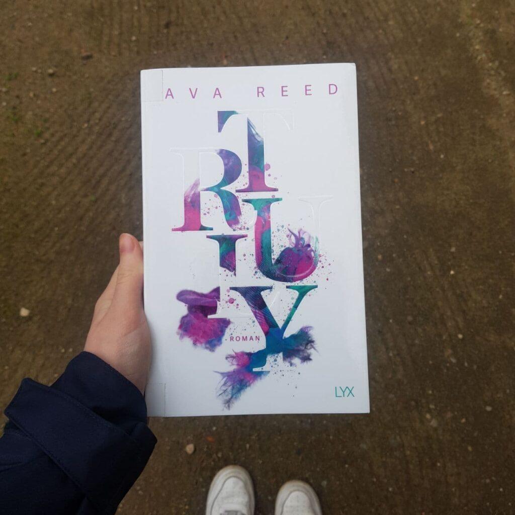 """Es handelt sich um ein Foto. Es ist eine Hand zu sehen, die das Buch hält. Das Cover des Buches ist weiß. Oben auf dem Cover steht in lila """"AVA REED"""". In der Mitte des Covers ist der Schriftzug """"TRULY"""" von oben nach unten. Der Schriftzug hat verschiedene Farben: lila, rosa, grün, blau. Zwischen den Buchstaben steht in kleinerer Schrift """"ROMAN"""". Unten rechts in der Ecke steht in türkis """"LYX""""."""
