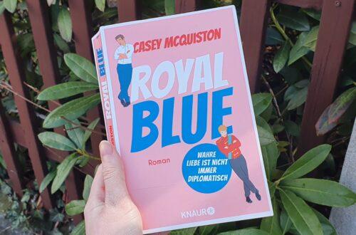 """Hand hält Buch. Buch hat ein Rosa Cover und den Titel """"Royal Blue"""". Außerdem sind 2 Männer auf dem Cover."""
