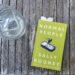 Das Buch liegt auf einem Holzuntergrund aus vertikalen Streben. Links daneben steht ein Wasserkrug.