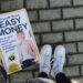 Hand hält Buch. Das Cover ist weiß und die Autorin ist auf dem Cover zu sehen. Über ihr steht der Titel des Buches. Im Hintergrund sieht man den Gehweg und weiße Schuhe.
